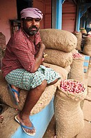 A porter resting on bags of shallots  Kollam, Kerala, India