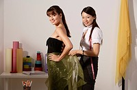 chinese fashion designer draping cloth around model´s waist, taking measurements