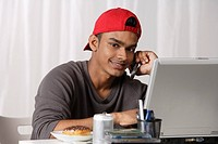 young man with red cap, talking on phone and working on laptop