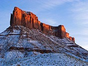 Sandstone butte in Castle Valley awash in alpenglow at sunset on a cold winter afternoon near Moab, Utah, USA