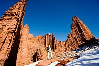 Female hiker admires the beautiful sandstone spires from trail at Fisher Towers outside Moab, Utah, USA