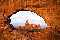Pre-sunrise alpenglow paints North Window and Turret Arch in brilliant shades of red in Arches National Park, Moab, Utah