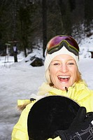 Laughing woman holding snowboard