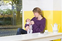 Young woman with baby on table