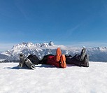 3 men lying in snow on top of mountain