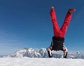 Man performing handstand on mountain