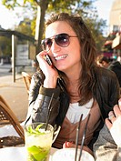 Woman on phone on terrace of café