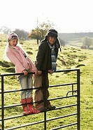 Girl and boy on gate in countryside
