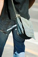 Person carrying denim shoulder bag, rear view, cropped