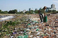 Person picking up trash on polluted shore, city in background