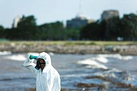 Person in protective suit looking at polluted water, side view