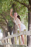 Girl standing on fence waving