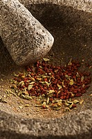 STILL LIFE Annato seeds and dried Mexican oregano in molcajete made from basalt rock with pestle for grinding spices and herbs
