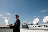 Businessman, serious, laptop, half portrait, side view, buildings, parabolic aerials,