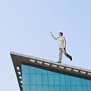 Low angle view of a businessman throwing a paper airplane