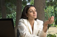 Businesswoman holding a plant and thinking