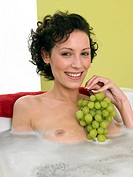 Woman with green grapes in bathtub