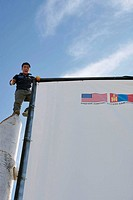 Mongolian workman puts up billboard encouraging Mongolian and American cooperation, Ulaan Baatar, Mongolia No release available