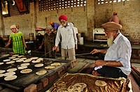 Sikh volunteers cooking chapatti for the poor at Gurdwara Shri Bangla Sahib Delhi, India