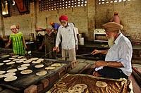 Sikh volunteers cooking chapatti for the poor at Gurdwara Shri Bangla Sahib Delhi, India