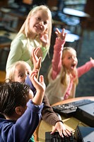 Elementary school kids with arms raised at computer in library
