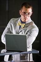 Portrait of serious businessman wearing bow tie and glasses, with laptop
