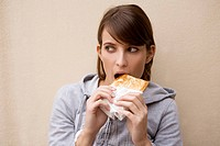 young woman eating a toasted sandwich