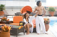 Portrait of African American couple on rooftop terrace with swimming pool in city
