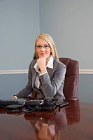 Portrait of young businesswoman sitting at desk, looking at camera
