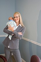 Portrait of young businesswoman holding baby in arms at work