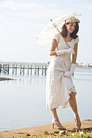 Portrait of elegant lady in white dress holding umbrella on water´s edge at a garden party