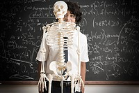 Boy and skeleton in front of blackboard