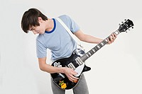 A teenage boy playing a guitar