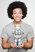 Portrait of a young man holding a robot