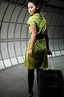 A young woman pulling a suitcase
