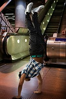 A man doing a handstand on the underground