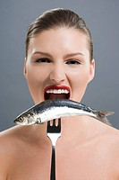 Woman biting a fish on a fork