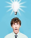A young man looking at an energy saving lightbulb