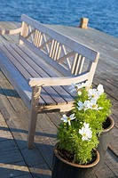 Finland, Aland Island, Silverskär Wood seat and flowers at small dock