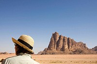 Jordan, Wadi Rum Desert Woman tourist at The Seven Pillars of Wisdom This are the most famous mountains of Wadi Rum, which owes its name to TE Lawrenc...
