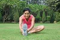 Woman stretching in a park, Gurgaon, Haryana, India