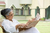 Woman reading a newspaper in a lawn, New Delhi, India
