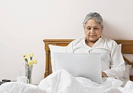 Woman working on a laptop on the bed