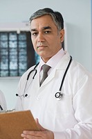 Portrait of a doctor holding a clipboard, Gurgaon, Haryana, India
