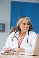 Female doctor using a laptop and writing prescription, Gurgaon, Haryana, India