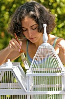 Hispanic woman painting birdcage