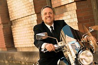 Man in suit sitting on motorcycle
