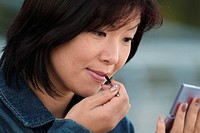 Asian woman putting on lipstick