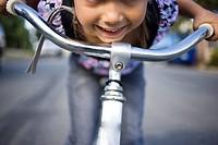 Girl leaning over bicycle handlebars