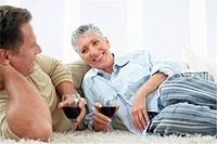 Couple drinking wine on rug in home (thumbnail)